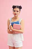 Photo of pretty student girl 20s with double buns hairstyle wearing  backpack holding many studying books isolated over pink background