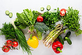Fresh green vegetables and summer produce on white surface