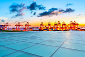 Empty floor and industrial container terminal at beautiful sunset in Shanghai.