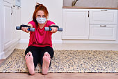 A woman does exercises with dumbbells in the home kitchen, lifestyle. A girl in a protective mask on isolation from the coronavirus epidemic