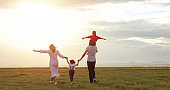 Asian family walking and running on the Meadow at sunset with happy emotion. Family, Holiday and Travel concept.