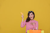 Portrait Asian beautiful happy young woman with sunglasses smiling cheerful and she is holding credit card and using smart phone for shopping online with shopping bags on yellow background.Happiness, consumerism, sale and people shopping concept