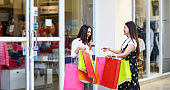 Asian women with friend are holding shopping bags and using a smart phone and smiling while doing shopping in the supermarket/mall