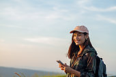 women asian with bright backpack looking at a map. View from back of the tourist traveler on background mountain, Female hands using smartphone, holding gadget