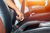 Asian woman fastening seat belt in the car, safety concept