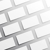 Mockup of horizontal business cards stacks arranged in rows at white textured paper background