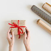 Hands holding a Christmas gift box wrapped in kraft paper and paper rolls on white table, top view. DIY gift wrapping. Eco-friendly present packaging