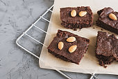 Homemade chocolate brownies with almond nuts served on a tray with baking paper, concrete background. Traditional American dessert
