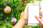 Close-up of female use smartphone blurred images with Colorful balls on Green Christmas tree background Decoration During Christmas and New Year.