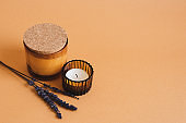 Aroma candles and dried lavender flowers on a background of orange color. Spa treatment and aromatherapy concept