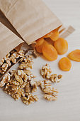 Dried apricot and raw walnut in small brown paper bags. Eco friendly biodegradable package and food storage