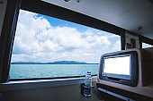 Inside of the bus which has LCD screen blank rear seat for entertainment with a bottle of water and window view of Beautiful landscape nature the sea with sky cloud, Figure tourism road trip concept.