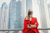 Young businesswoman in red suit wearing reusable face mask of black color standing near city center with skyscrapers. Strong and powerful female entrepreneur during Covid 19 or coronavirus pandemic. Strong woman concept