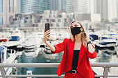 Young blond woman in red suit and with protective face mask taking a selfie photo near luxury yachts and skyscrapers. New normal concept