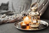 Golden lantern and burning candles on a metal tray. Traditional decor for Muslim holidays. Eid Al Adha celebration. Ramadan