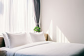 Close-up of white pillow on bed decoration with light lamp and green tree in flowerpots in hotel bedroom interior.