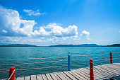 bridge wooden walking way in the sea at Hat chao lao beach blue sky background in Chanthaburi, Thailand.