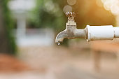 Water flowing from old rusty faucet with blur green the park background in outdoor,consumption concept.
