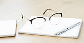 Close-up of glasses with a notebook on the table. Working space