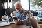 Mature businessman using mobile phone. Mid adult entrepreneur using mobile phone at restaurant. Confident and smiling businessman working on mobile phone at restaurant.