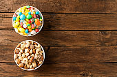 Diet decision concept. Mixed nuts and sweet in bowls on wooden background. Top view