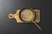 Frying pan on wooden board. Top view