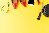 Fashion background. Red high heels, purse, phone, eyeglasses and nail polish on yellow table. Flat lay