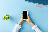 Woman's hands using smart phone with empty screen on blue table. Office desktop. Flat lay