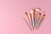 Collection of makeup brushes on pink background