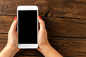 Woman's hands holding smartphone with copyspace. Top view
