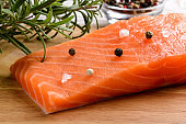 Close-up of raw chilled salmon fillet, pepper grain, sea salt and rosemary on a wood cutting board. Healthy eating, seafood recipe ingredient and organic omega 3 source concepts.
