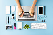 Woman's hands working on laptop on blue table with accessories. Modern workspace. Flat lay