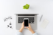Overhead shot of female hands using smartphone with blank screen over laptop on white background. Office desktop. Flat lay