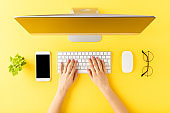 Office desktop concept. Woman's hands working on computer with business accessories on yellow background. Top view