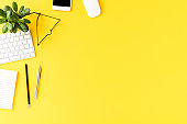 Elegant office desktop with business accessories on yellow background with copyspace. Top view