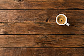 Overhead shot of hot coffee cup on wooden background with copyspace