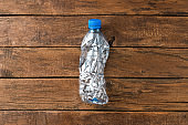 Used and crushed small bottle of water on rustic wooden background. Plastic recycling. Top view