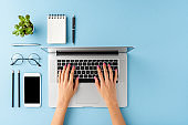 Woman's hands using laptop on blue table with accessories. Business background with copyspace. Top view