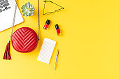 Red woman's purse with laptop, cosmetics, notebook, eyeglasses and flower on yellow background with copyspace. Shopping online concept. Flat lay