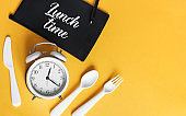 White Alarm clock with knife fork and spoon for mealtime or diet concept on yellow background, free space for text.
