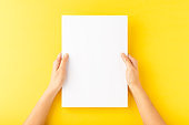 Young woman's hands showing blank paper sheet on yellow desktop. Top view