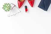 Fashion background with red high heels, purse, eyeglasses and nail polish isolated on white table. Woman's lifestyle. Top view