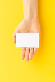 Woman's hand holding business card on yellow background. Mockup. Close up