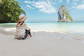Asian woman sitting on the beach looking at the amazing sea and enjoying with beautiful nature in her vacation
