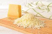 Heap of grated italian hard cheese Grana Padano or Parmesan on a wood cutting board over white wood table. Delicious ingredient for pizza, sandwiches, salads.