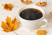 Large white mug of hot steaming coffee and few dry yellow fall leaves over white wood rustic surface. Cozy autumn mood concept.