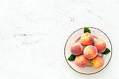 Summer fruits. Ripe red peaches on plate on white table top-down copy space