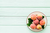Summer fruits. Ripe red peaches on plate on green wooden table top-down copy space