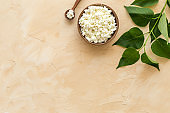 Cottage cheese in wooden bowl on beige table top view copy space