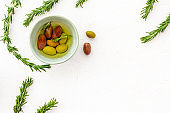 Olives in bowl near rosemary on white table top view copy space
